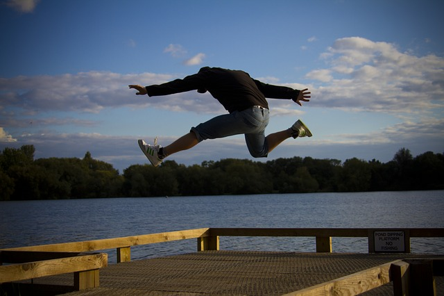 A man jumps with excitement next to a river