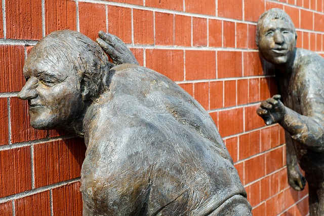 A bronze sculpture where two men keep their ears to a red brick wall, listening