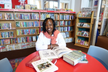 A middle aged black woman sits at a round red table, with books open in front of her. They are history books about Devon. She is wearing a white shirt, with a coral jumper tied around her shoulders. She has braided hair with a few beads in it, and is smiling broadly at the camera. Behind her are shelves of books. She is in a library.