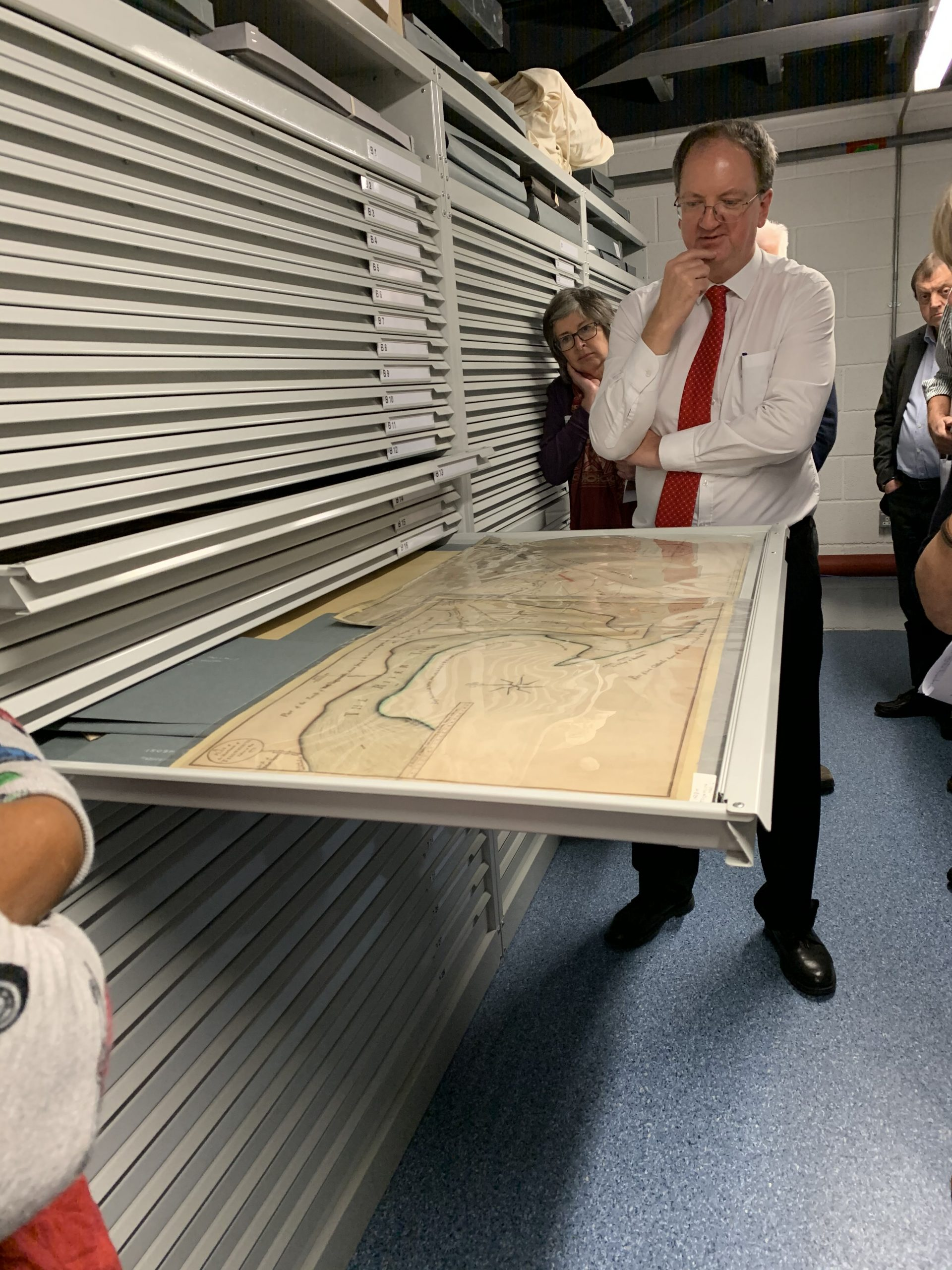 Brian, wearing a white shirt and red tie, stands in front of a large archival draw which he has opened to reveal an antique map of Devon. Volunteers stand behind him, looking in interest.