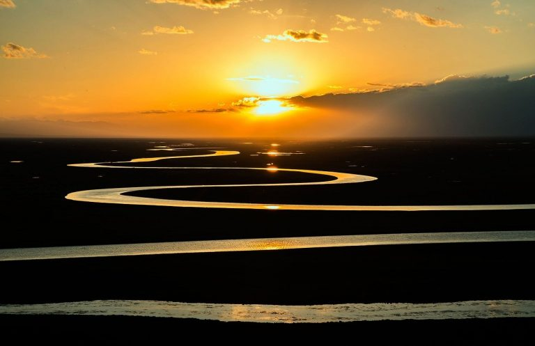A photograph of a sunrise. The sky is filled with orangey tones, and the sun is partly obscured by fine cloud. In the foreground, a river snakes away in a repeating 'S' shape: wider at the bottom and growing narrower as it moves toward the horizon at the top of the photograph.