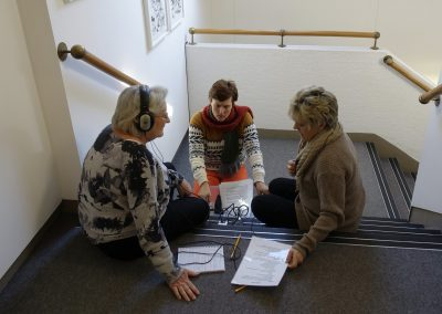 A range of photos of volunteers engaging with the oral history training. They are listening to each other, examining the recording equipment with interest, sitting against museum cases and smiling.