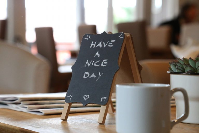 "A picture of a miniature blackboard saying ""Have a nice day"". In the foreground of the image is a cup of coffee."
